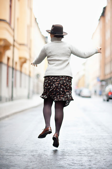 Woman jumping in the street.