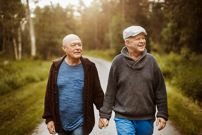masma46319, Happy gay couple looking away while walking on road amidst trees